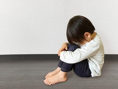 膝を抱え悲しむ少年