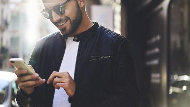男性が笑いながらスマホを触っている画像