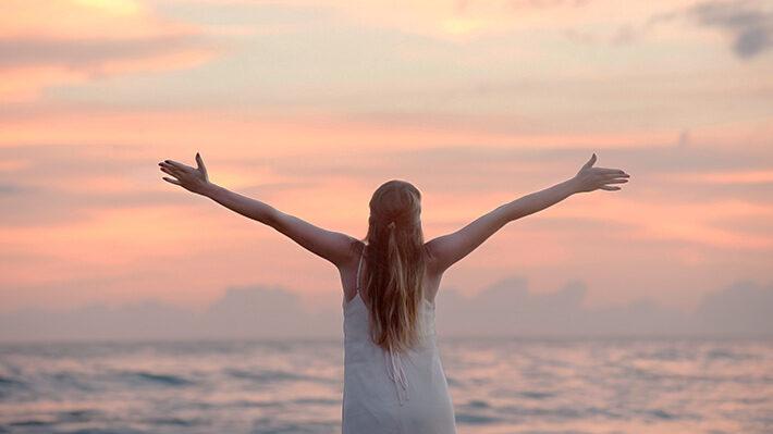 海にむかってバンザイする女性の画像