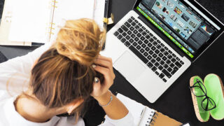 仕事と育児で頭を抱える女性の画像