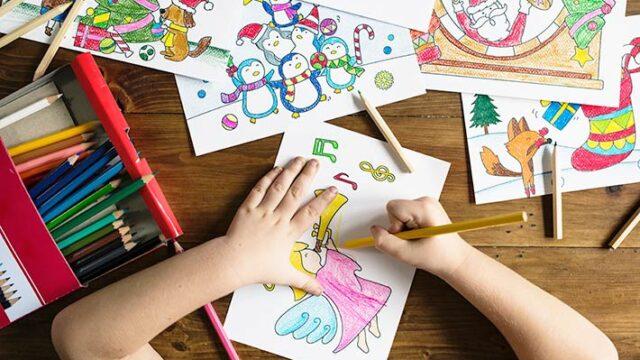 子どもが勉強机で塗り絵をしている