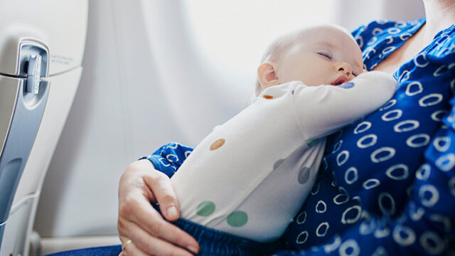 飛行機でママに抱かれ眠るこども