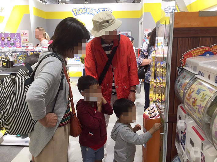 空港内のポケモンセンターで遊ぶ親子