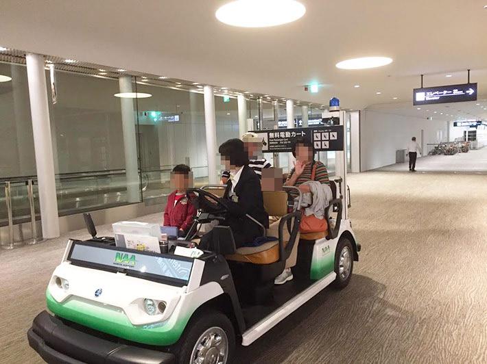 空港内のカートに乗る親子