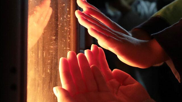 電気ストーブで温めている手